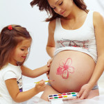 pregnant woman with cute daughter paint mom´s belly